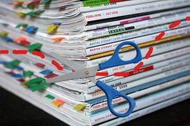 Tijeras recortando un bloque de revistas