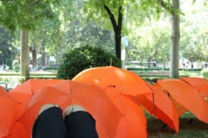 Paraguas rojos que simbolizan el fuego y son utilizados por las personas libro en sus narraciones.