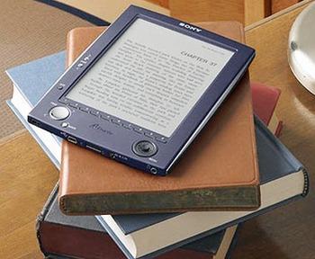 Lector de libros electrónicos sobre una pila de libros impresos