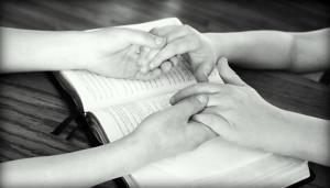 Sosteniendo manos sobre un llibro