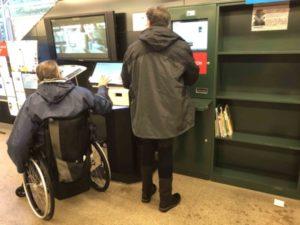 dos personas usuarias de la biblioteca hacen uso del autopréstamo a dos alturas. Una de ellas es usuaria de silla de ruedas.